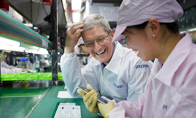 Apple CEO Tim Cook watches on as a Foxconn employee puts the finishing touches on an Apple iPhone 6 being built at a Foxconn factory - Tim Cook visits a Foxconn factory where the Apple iPhone 6 is built