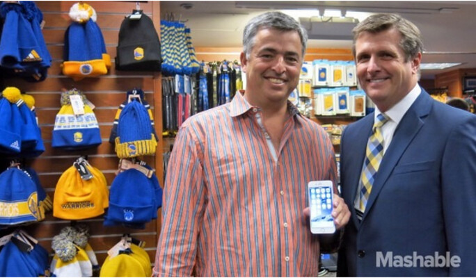Apple's Eddy Cue (L) poses with Warriors team president Rick Welts and an Apple iPhone 6 - Apple executive Cue helps Apple Pay debut at Oracle Arena