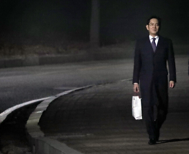 Jay Y. Lee exited the detention center, carrying a white shopping bag (courtesy of The Korea Herald). - Samsung's boss walks free, prosecutors still on his case