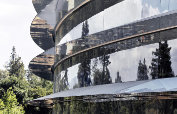 Curved glass encompassing the ring-shaped building reflects the surrounding vegetation.