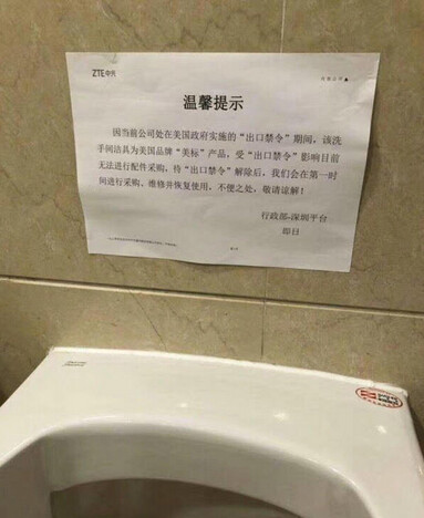 Sign above broken urinal at ZTE facility says that the company must wait for the U.S. export ban to be lifted before it can be fixed - ZTE remains in limbo, caught between deal with White House and possible legislation