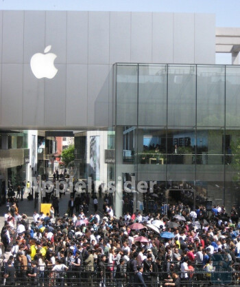 Long lines wait outside an Apple Store in China for the Apple iPad 2