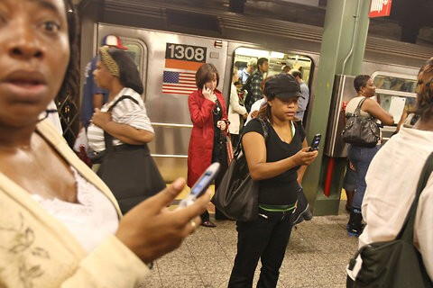 New Yorkers trying to use their cell phone on a Brooklyn subway platform in 2007; starting Tuesday in certain locations, AT&T and T-Mobile users will be able to get a signal - Some NYC subway platforms to support AT&T and T-Mobile service starting Tuesday