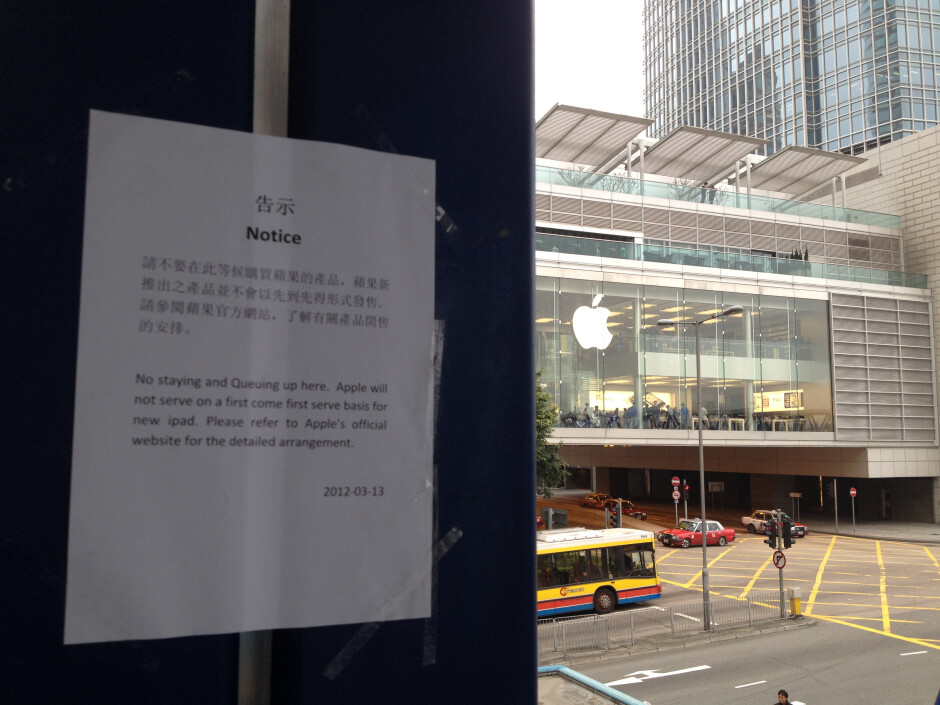 While posts say no lines are allowed at the Hong Kong Apple Store (L), the crowd has moved to a footbridge hundreds of yards away (R) - Signs posted around Hong Kong Apple Store say new iPad won't be sold on first-come first-served basis