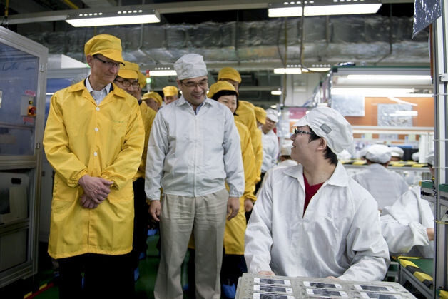 Tim Cook at the iPhone production line in the Foxconn plants - Tim Cook shakes hands with the Chinese VP en route to the Foxconn facilities