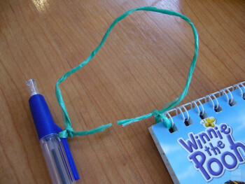 Attach the pen to the sketch pad with the other piece of string