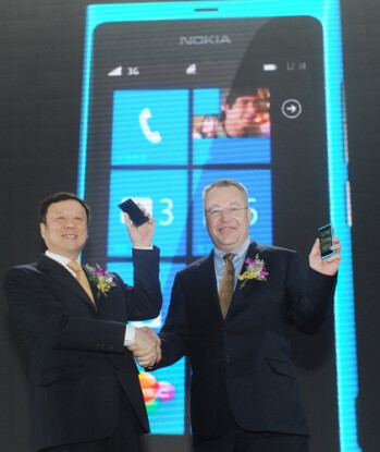 At right, Nokia executives celebrate the CDMA powered Nokia Lumia 800C in China, Verizon's lone Windows Phone model is the HTC Trophy (L)