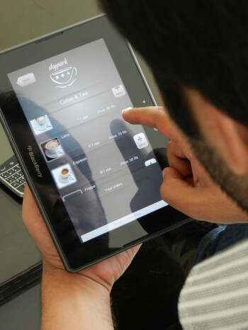 At the SkyPark Cafe, BlackBerry PlayBooks are used by waiters (L) while a tablet powers the juke-box