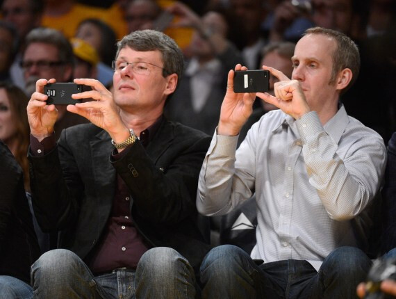 Heins and Bocking snap away (L) while Heins poses with his BlackBerry PlayBook - RIM CEO Heins brings a BlackBerry 10 handset courtside
