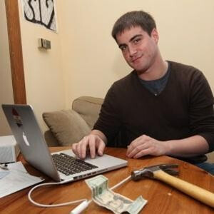Nadav Nirenberg poses with the hammer and a $20 bill, the tools he used to get his phone back