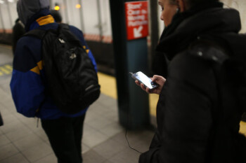A New Yorker checks her Apple iPhone on a subway platform