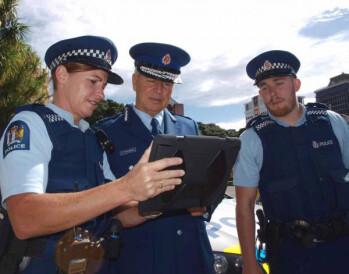 New Zealand Police Commissioner Peter Marshall checks out an Apple iPad during the trial