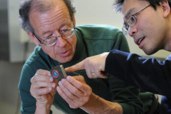 Engineers Arto Nurmikko and Ming Yin examine their prototype wireless, broadband neural sensing device.	 Credit - Fred Field for Brown University