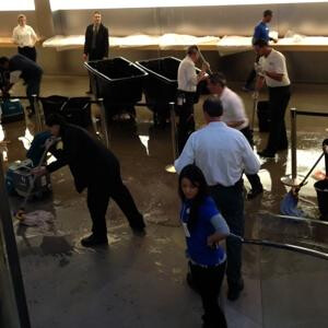 Workers mop up at the Fifth Avenue Apple Store following a flood