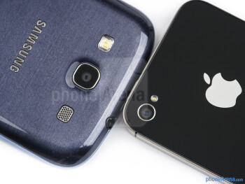 Rear cameras - The sides of the Samsung Galaxy S III (bottom, left) and the Apple iPhone 4S (top, right) - Samsung Galaxy S III vs