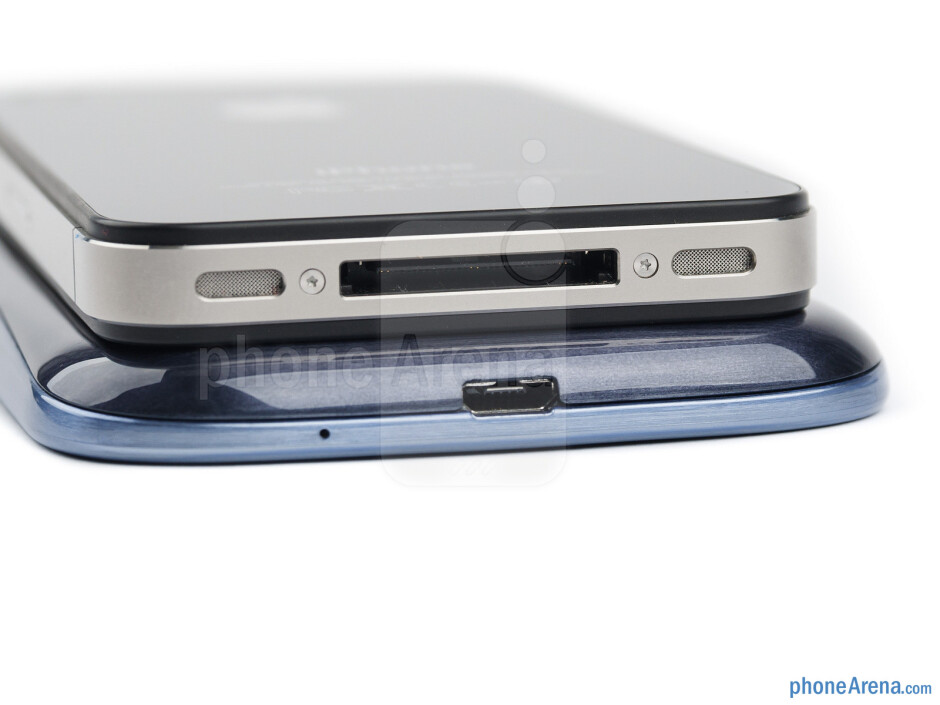 Bottom edges - The sides of the Samsung Galaxy S III (bottom, left) and the Apple iPhone 4S (top, right) - Samsung Galaxy S III vs Apple iPhone 4S